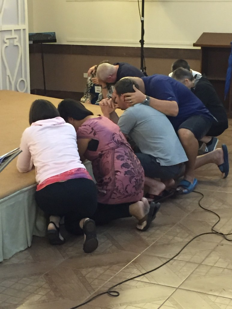 Missionaries Dar Li, Louela Page, Sam Freeman, Lisa and Fil Kakilala and Danny and Rita Ballard pray after an evening service